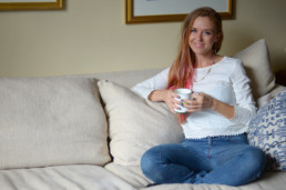 Caitlin Padgett, your coach for drinking less alcohol, enjoys a cup of tea on the couch.